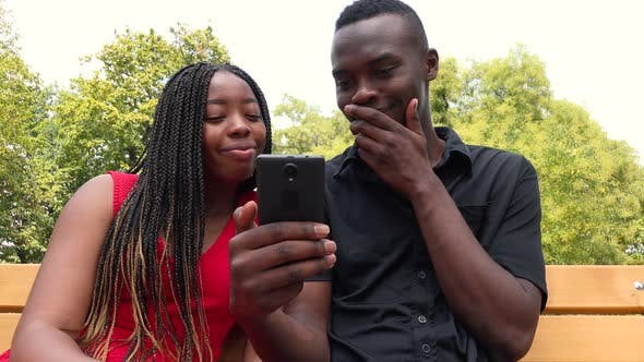 Thumbnail for A Black Man and a Black Woman Sit on a Bench in a Park, Look at a Smartphone and Laugh