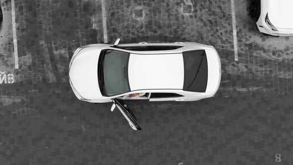 Thumbnail for Aerial View Woman in a White Fur Coat Gets Out of a White Car and Puts It on the Alarm
