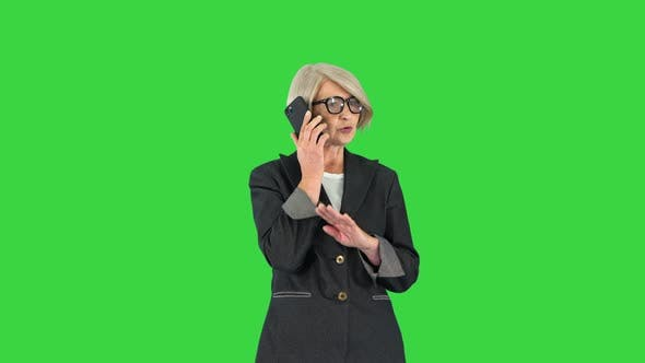 Stylish Focused Busy Greyhaired Lady Ceo Boss Chief Calling on a Green Screen Chroma Key