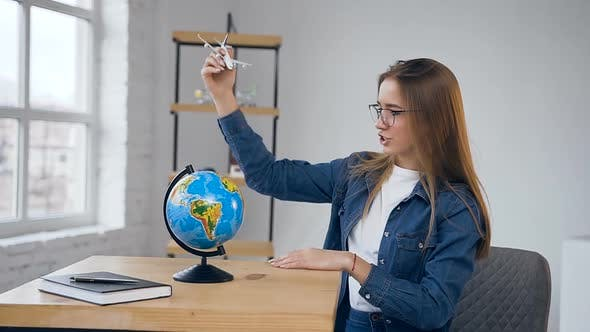 Thumbnail for Young Exciting Woman Moving Toy Plane Around the Globe.