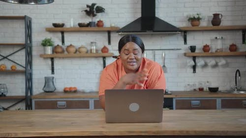 Body Positive Black Woman Calls Via Laptop and Waves Hello