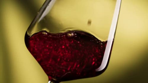 Wine Pouring in Wine Glass at Yellow Background