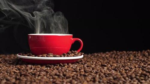 Kaffeetasse mit Rauch und Kaffeebohnen