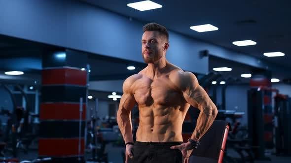 Brutaler starker Bodybuilder, der Muskeln aufpumpt. Bodybuilding und Indoor-Sportkonzept
