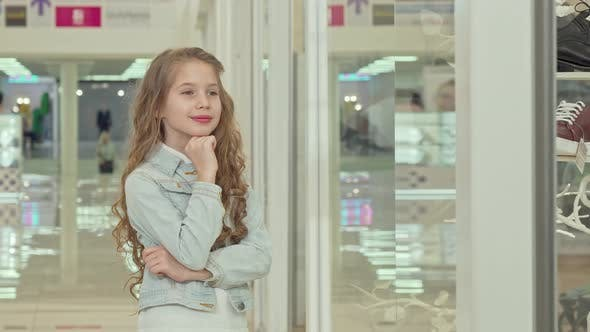Thumbnail for Cute Little Girl Smiling To the Camera, Examining Fashion Store Display