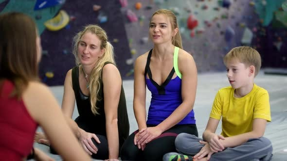 Thumbnail for Caucasian Climbers Discussing Practice with Female Coach at Gym