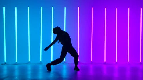 Young Woman Dancing Street Dance Hip Hop in a Studio with Neon Lighting Tube on a Blue Purple