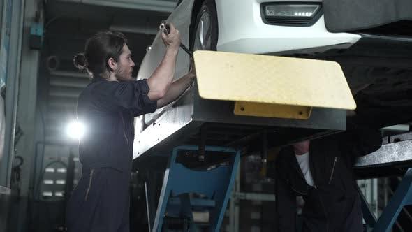männlicher Mechaniker überprüft und repariert den Motor beim Autowerkstattservice, Automobiltechniker