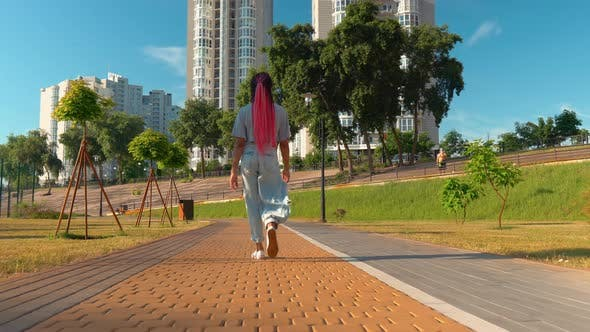Thumbnail for Rear Young African American Woman Walks in Sunny Day Sidewalk