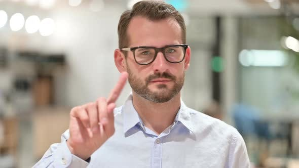 Cover Image for Portrait of Serious Businessman Saying No By Finger Sign