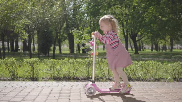 Thumbnail for Cute Adorable Small Funny Girl in Pink Dress Riding a Scooter in the Park. Camera Following the