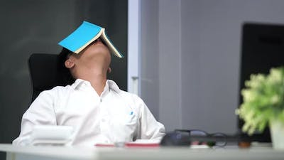 young stressed man studying with book and laptop