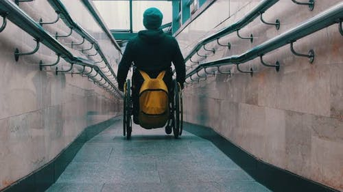 Disabled Man in Wheelchair Carefully Getting Down the Long Ramp
