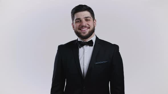 Cheerful Man with Beard in Official Wear  Tuxedo Nods His Head Approvingly