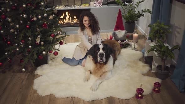 Thumbnail for Lächelnd brünette kaukasische Mädchen sitzend mit großen Hund auf weichem Teppich vor dem Kamin. Dekoriert