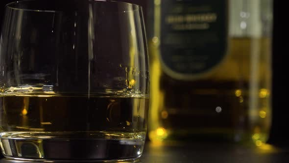 Thumbnail for Closeup on a Glass of Whiskey - a Bottle in the Blurry Background