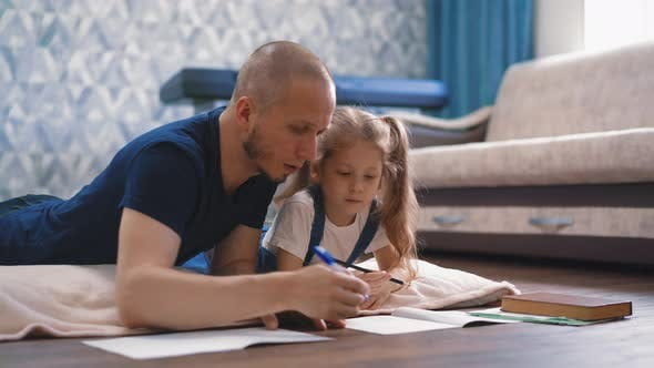 Thumbnail for Parent Helps Daughter with Ponytails Do Homework at Home