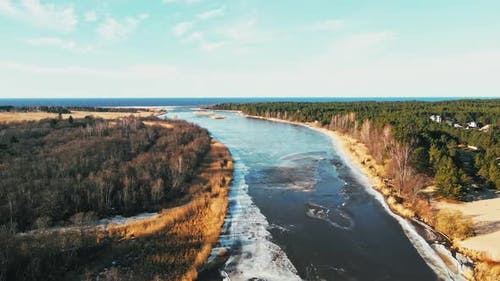 Spring Aerial View Over River Joining Baltic Sea with Melting Ice and Snow