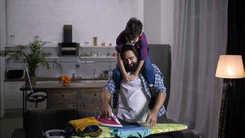 Caring Father with Son on Shoulder Ironing Clothes