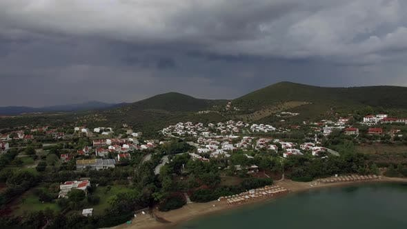 Thumbnail for Flying Over Sea, Beach and Cottages in Resort Town of Greece on Overcast Day