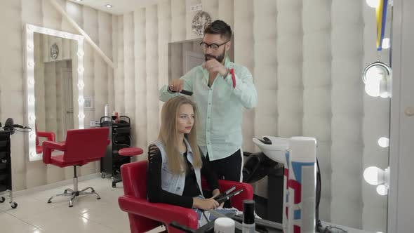 Professional Hairdresser Styling Combing Model Hair. Making Volume Hairstyle