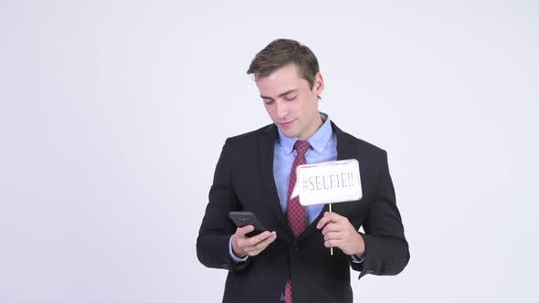 Cover Image for Young Happy Handsome Businessman Taking Selfie with Paper Sign