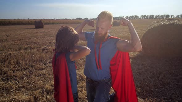 Dad and Son As Superheroes Showing Biceps Outdoors