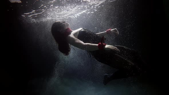A Darkhaired Woman in Red Handcuffs Swims Deep Under the Water on a Dark Background She Soars