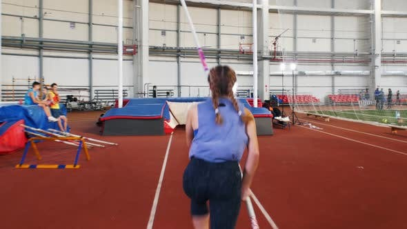 Thumbnail for Pole Vaulting in the Indoors Stadium - Young Woman with Pigtails Jumping Over the Bar