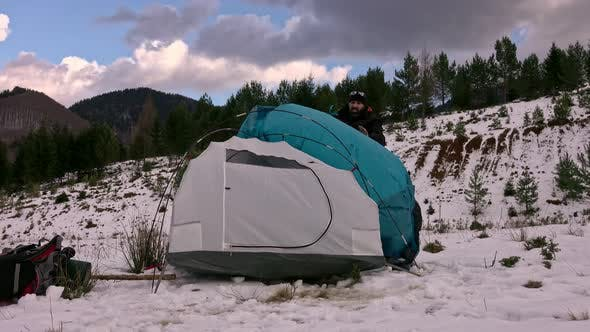 Hiker pitching tent in winter in the mountains.