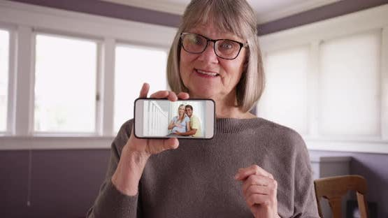 Charming old female showing video of pregnant daughter with husband on phone