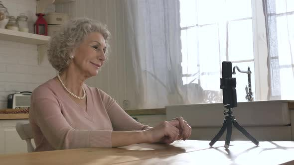 Nice Elderly Woman Tells Story Against Smartphone on Tripod