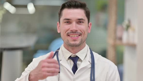 Positive Young Male Doctor Showing Thumbs Up Sign