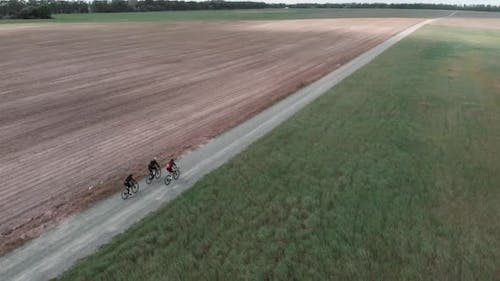 People riding on bikes on gravel road. Cycling on gravel roads