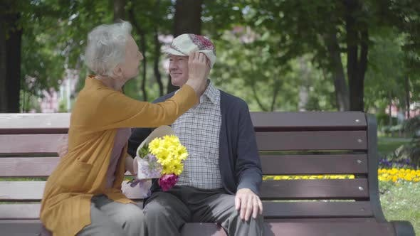 Thumbnail for Old Man Kissing His Woman with Flowers on the Banch in a Spring Park