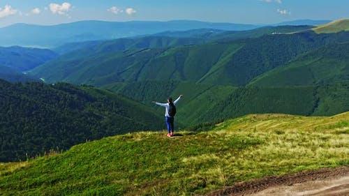 Traveler Raising Hands Looking in Nature Scene