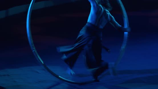 Thumbnail for Muscular Man with Long Hair Is Doing Wheel Gymnastics in Dark Blue Lights