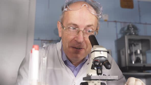 Shocked Senior Scientist Man Is Surprised By Liquid in Tube