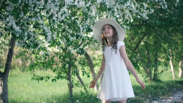 Thumbnail for Daydreaming Young Girl Standing Under Blooming Spring Trees