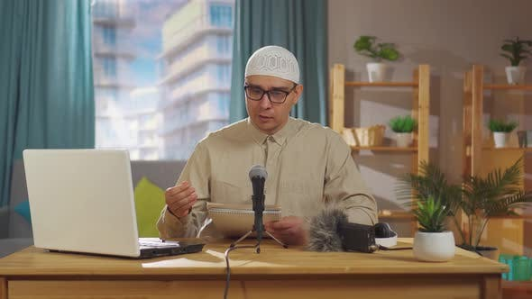 Muslim Man in a Skullcap Records a Podcast While Sitting in Front of a Microphone in Living Room