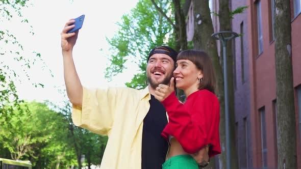 Happy Cute Couple Having Video Call on the Modern Street