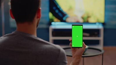 Person with Modern Smartphone Looking at Green Screen