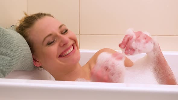 Thumbnail for A young beautiful woman plays with foam in a bathtub - closeup