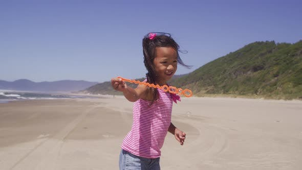 Cover Image for Young girl playing with bubbles at beach