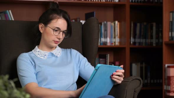 Thumbnail for Young Attractive Business Woman with Tablet Computer in Librory Office Bookshelf Background
