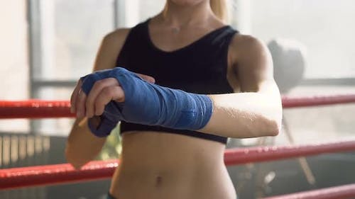Young Woman Wrapping Blue Bandages