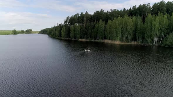 Aerial view of lake with equipped fishing piers and two fishermens in a boat fishing.