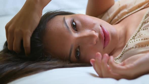 Beautiful latina woman lying in bed