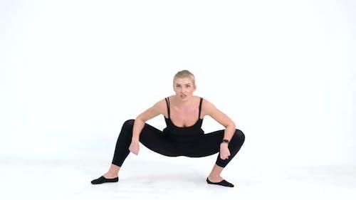 Slim Fit Fitness Girl führt eine Reihe von Übungen auf grauem Hintergrund durch