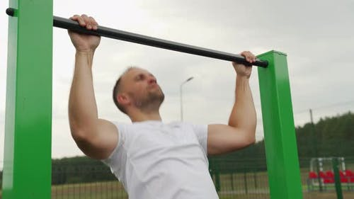 Strong Man From Behind Doing Pull Ups on Horizontal Bar